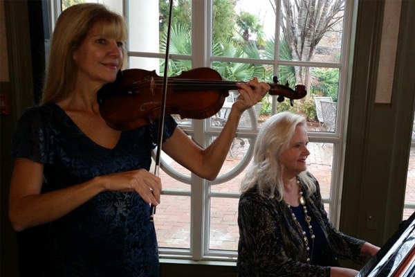Christine playing violin with piano